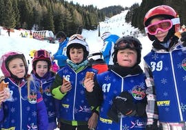 A group of happy kids at the end of their Kids Ski Lessons (5-14 years) for All Levels with the ski school Scuola di sci e snowboard Alpe Cimbra.