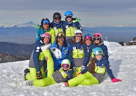 Children posing for a photo with their instructor of the ski and snowboard school Scuola di Sci e Snowboard Prato Nevoso at the end of their Kids Ski Lessons (5-14 y.) for All Levels.