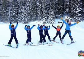 A group of children learns to ski during Kids Ski Lessons (5-14 years) in the Holidays for All Levels with the ski school Scuola di sci e snowboard Alpe Cimbra.