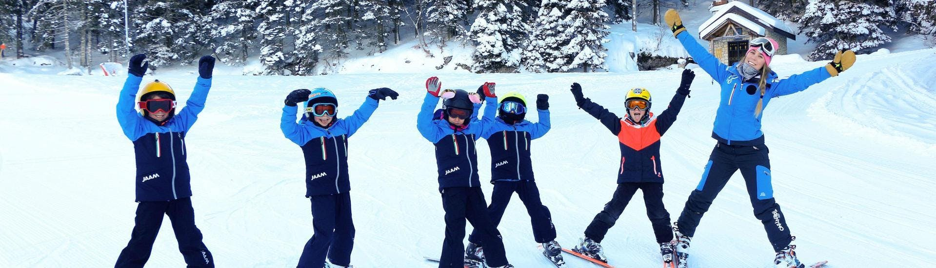 A group of kids is enjoying one of their ski lessons with their ski instructor from the ski school Scuola di Sci e Snowboard Alpe Cimbra in the ski resort of Folgaria.