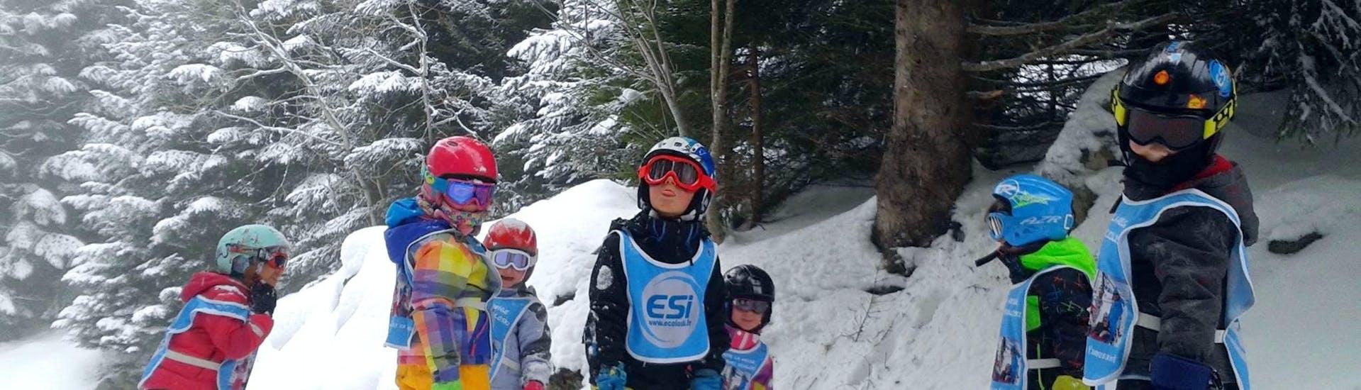 Los niños están parados en medios de las pistas rodeados de árboles durante sus clases de esquí para niños (5-15 años) - Tarde con la escuela de esquí ESI Ecoloski Barèges.