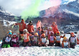 A group of kids and their instructors from the ski school Scuola Sci Cortina are having fun after skiing during Kids Ski Lessons (5-15 years) - With experience.