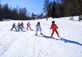 A grouf of kids is improving their skills on the slope during Kids Ski Lessons (5-15 years) - With Experience with the ski school Scuola di Sci e Snowboard Cristallo Cortina.