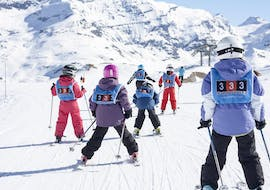 Young skiers are skiing down a snow slopes during their Kids Ski Lessons (5-17 years) - Afternoon - All Levels with the 333 ski school in Tignes.