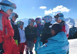 A groupe of kids is gathered around their ski instructor from the ski school ESI Easy2Ride Morzine before their Kids Ski Lessons + Ski Pass (5-6 y.) - Afternoon - Beginner.