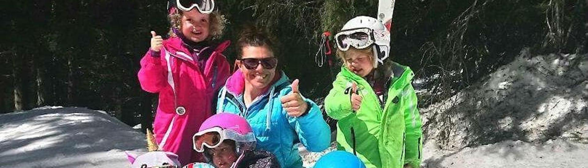 Un groupe d'enfants sourient à la caméra, le pouce levé, autour de leur moniteur de ski de l'école de ski ESI Easy2Ride Morzine pendant leur Cours de ski Enfants + Forfait (5-6ans) - Journée - Débutant.