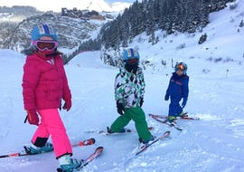 A group of children is facing the camera before hitting the slope during their Kids Ski Lessons + Ski Pass (5-6 y.) - Morning - Beginner with the ski school ESI Easy2Ride Morzine.