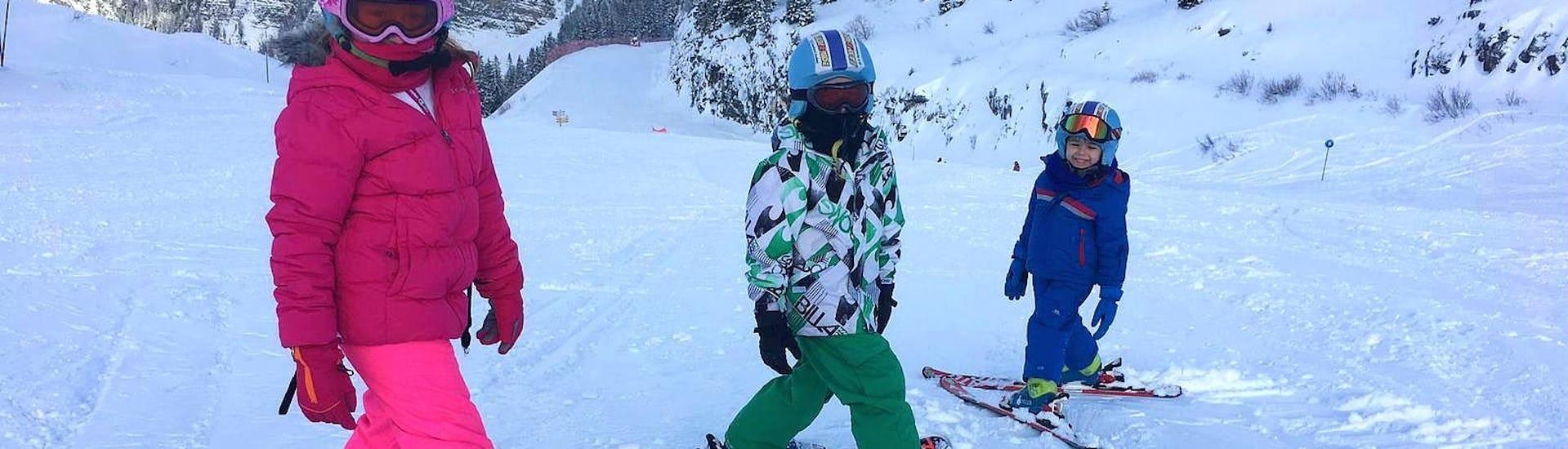 Un groupe d'enfants fait face à l'appareil photo avant de s'élancer sur la piste pendant leur Cours de ski Enfants + Forfait (5-6 ans) - Matin - Débutant avec l'école de ski ESI Easy2Ride Morzine.