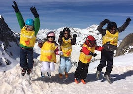 Kids are jumping in the air as they are happy to attend their Kids Ski Lessons (5-8 years) - Morning - 1st Timer with the ski school ESI du Tourmalet in La Mongie.