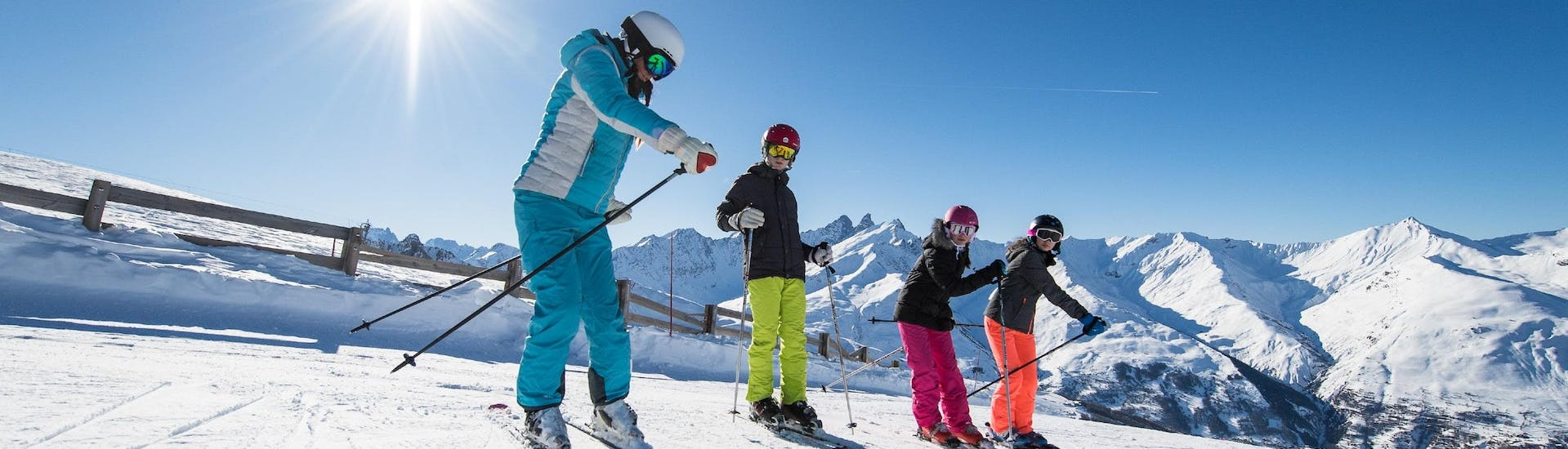 A ski instructor from ESI Alpe d'Huez - European Ski School is showing participants the right gestures during their Kids Ski Lessons (6-12 y.) for All Levels.