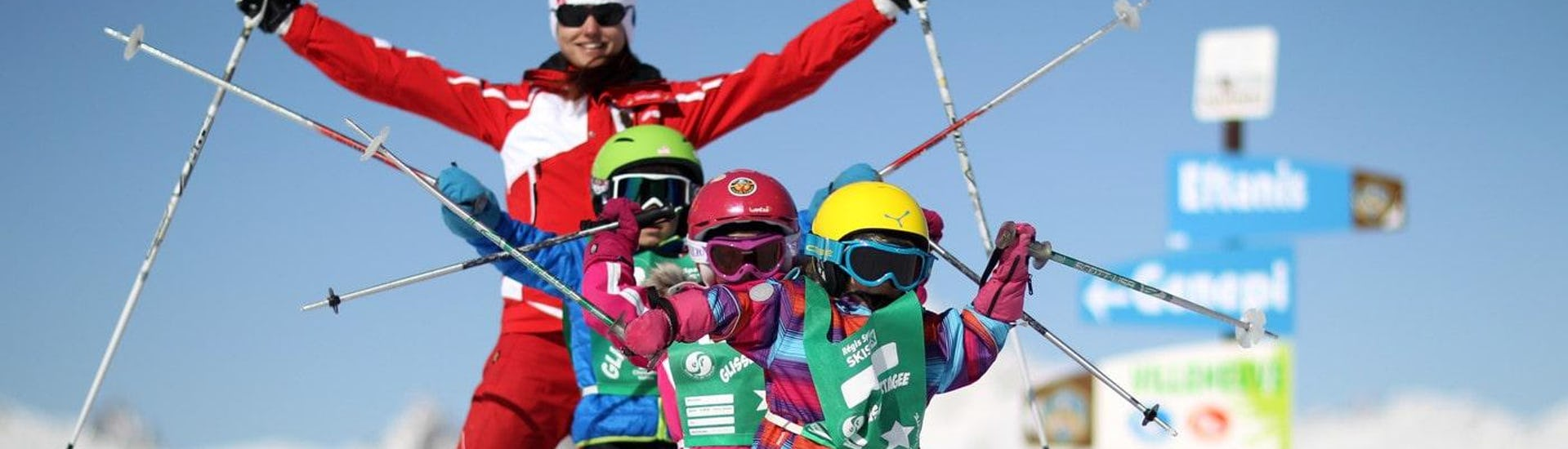 Kids are standing one behind the other with their ski poles up in the air during their Kids Ski Lessons (6-12 years) - Beginner with the ski school ESF Alpe d'Huez.