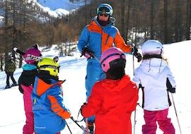 Eine Gruppe von jungen Skifahrern hört bei der von der Skischule YES Academy Sestriere angebotenen Aktivität Kinder Skikurs (6-12 J.) - Anfänger ihrem Skilehrer aufmerksam zu.