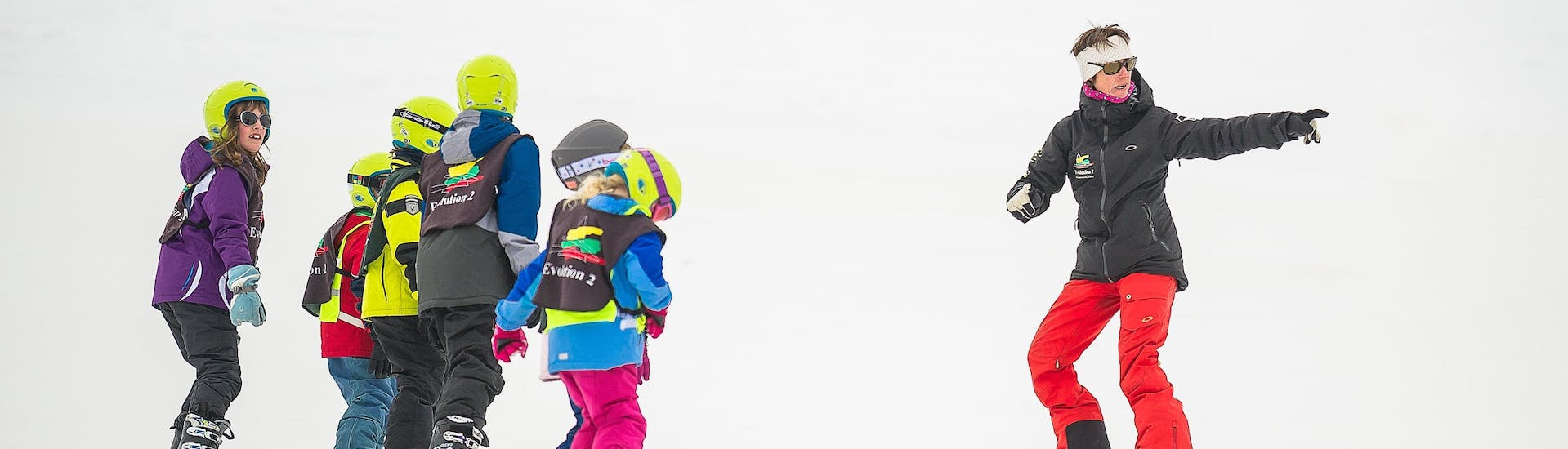 A group of skiers are following the instructions of their ski instructor from the ski school Evolution 2 Tignes during their Kids Ski Lessons (6-13 years) - Afternoon - All Levels.