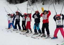 A group of participants of the Kids Ski Lessons (6-13 y.) - First Timer organized by the ski school Scuola di Sci Val Rendena in the ski resort of Pinzolo is having fun on the snowy slopes.