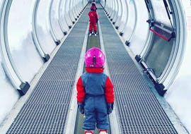 Children are taking the magic carpet before starting their Kids Ski Lessons (6-13 years) - Low Season - 1st Timer with the ski school Evolution 2 Super Besse.