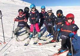 Children are standing at the top of a slope before heading down during their Kids Ski Lessons (6-13 years) - February 9-14 - All Levels with the ski school Evolution 2 Super Besse.