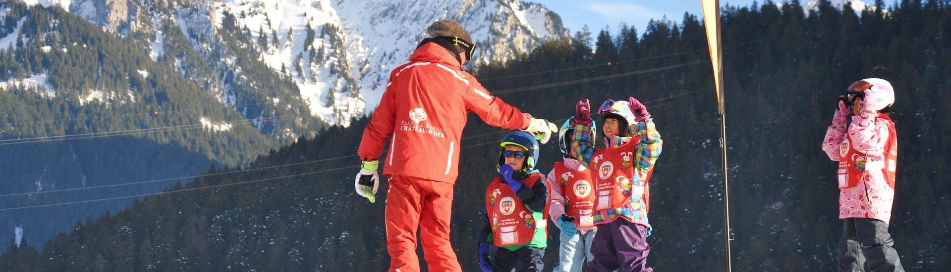 Les enfants suivent les instructions de leur moniteur de ski pendant leur Cours de ski Enfants (6-14 ans) depuis Bulle avec l'école de ski ESS Château d'Oex.