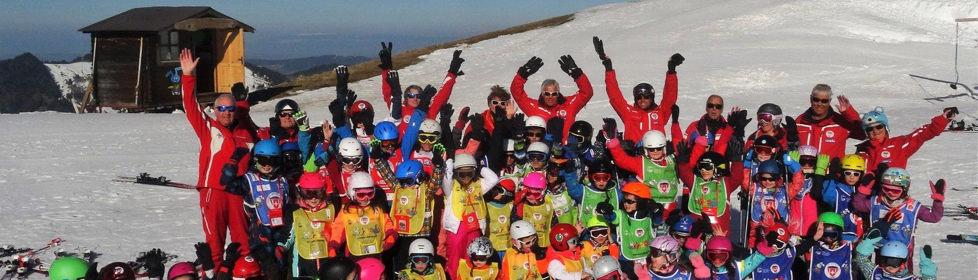 Students from the the swiss ski school Charmey and their ski instructors are gathered for a group photo celebrating their Kids Ski Lessons (6-15 years) - 4 lessons - All Levels.