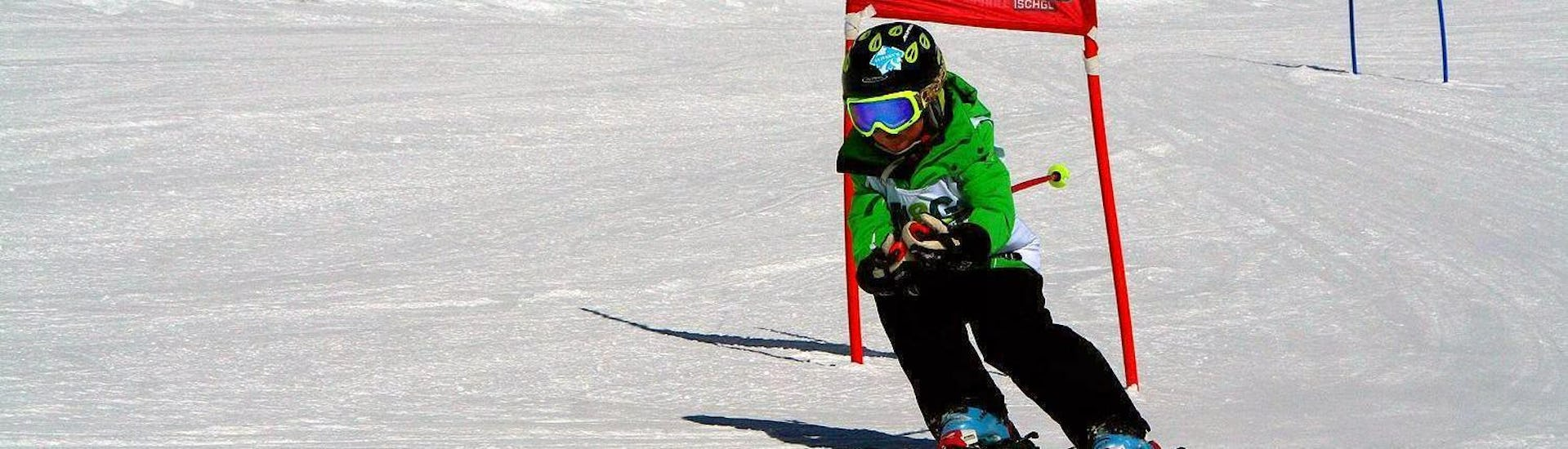 A young child is speeding down a race track during one of their Kids Ski Lessons (6-15 years) - Advanced in the ski resort of Ischgl.