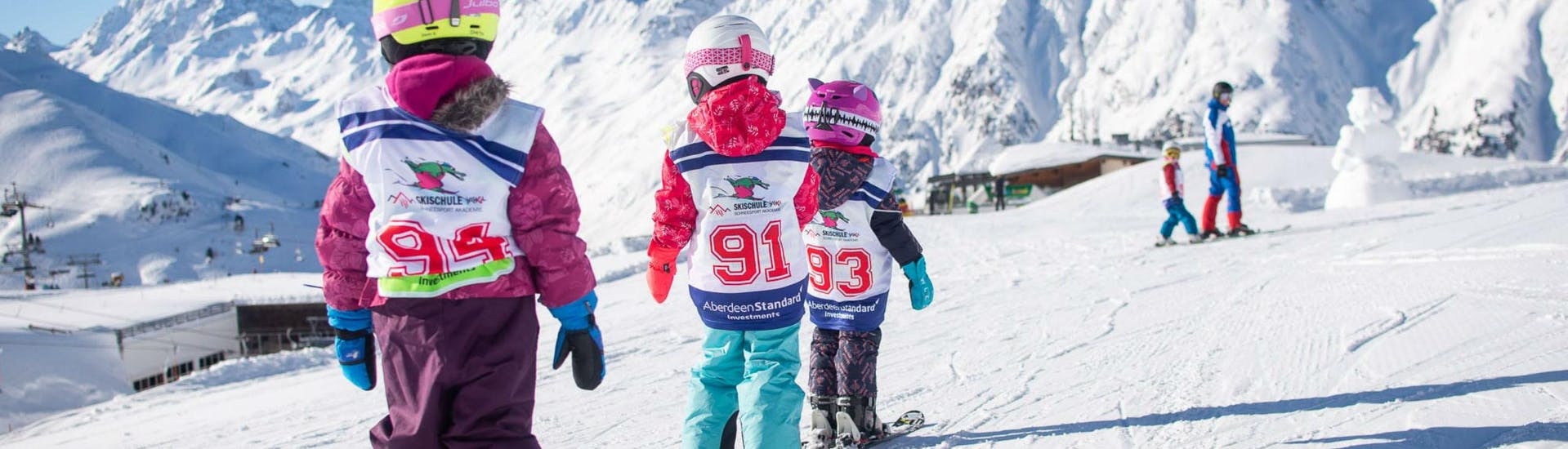 Three young kids are sking in a row behind one another along a flat plane of snow during their Kids Ski Lessons (6-15 years) - First Timer in the ski resort of Ischgl.