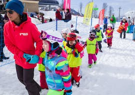 A group of children is preparing to ski during the kids' ski lessons (6-17 years old) for without experience held by the Abetone Ski School.