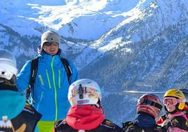 A group of children is listening carefully to their ski instructor from the ski school Evolution 2 Val d'Isère during their Kids Ski Lessons (6-18 years) - Afternoon - All Levels.