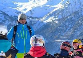 Un groupe d'enfants écoute attentivement leur moniteur de ski de l'école de ski Evolution 2 Val d'Isère pendant leur Cours de ski Enfants (6-18 ans) - Après-midi - Tous niveaux.