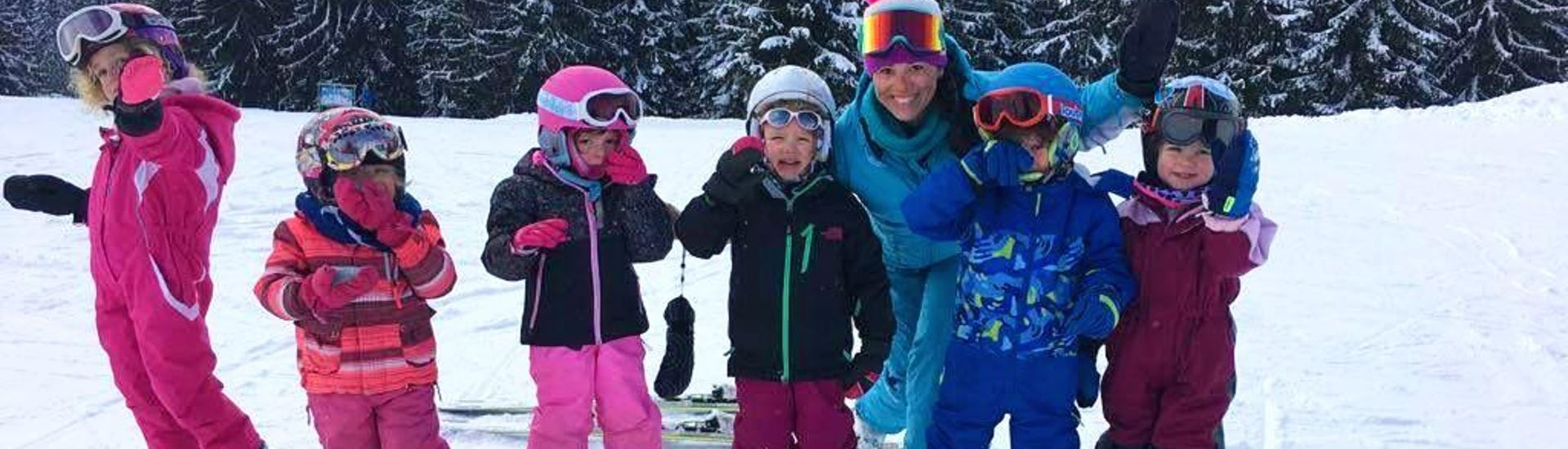 A group of kids is smiling at the camera in front of snowy trees together with their ski instructor from the ski school ESI Easy2Ride Morzine during their Kids Ski Lessons + Ski Pass (7-12 y.) - Full Day - Beginner.