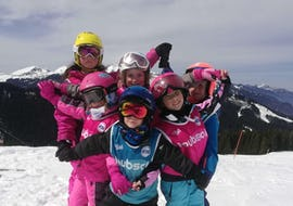 A group of kids is smiling at the camera at the top of the mountain during their Kids Ski Lessons + Ski Pass (7-12 y.) - Morning - Beginner with the ski school ESI Easy2Ride Morzine.