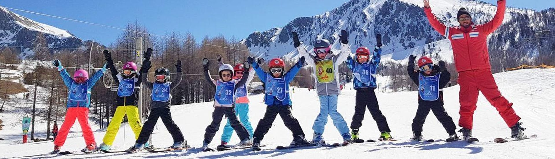 Kids are standing next to each other at the bottom of a slope, happy to start learning how to ski during their Kids Ski Lessons (7-12 y.) for All Levels with the ski school ESF Isola 2000.