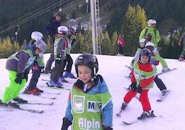 Little children are learning how to ski in the Kids Ski Lessons (7-8 years) - Beginners under the supervision of an instructor from the school Alpin Skischule Oberstdorf.