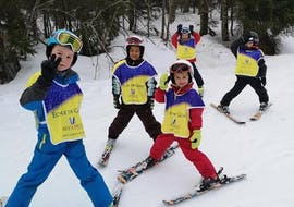 Eine Gruppe Kinder winkt beim Kinder Skikurs (8-12 Jahre) - Ferien - Anfänger mit der Skischule Moonshot La Bresse in die Kamera.