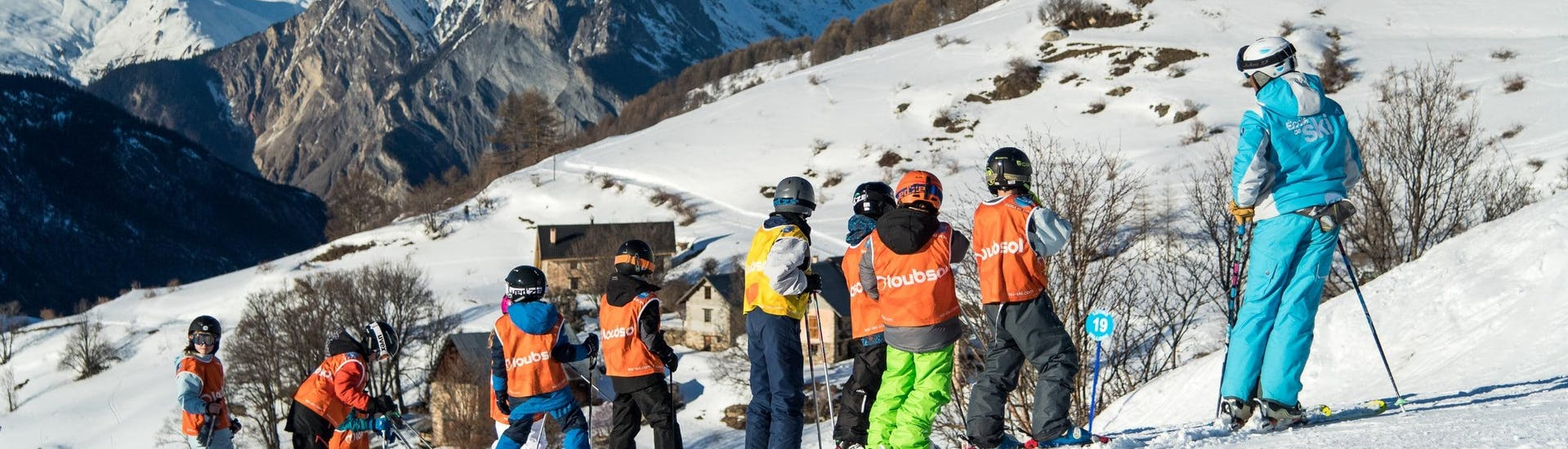 Young skiers are standing in the middle of a beautiful winter landscape during their Kids Ski Lessons (8-15 years) - All Levels with the ski school ESI Dévoluy.