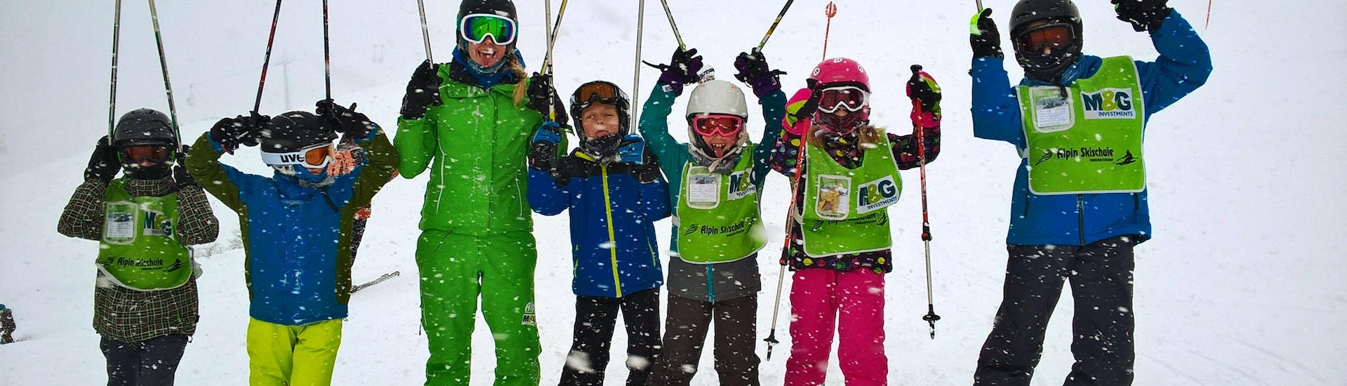A group of happy children during the Kids Ski Lessons (9-16 years) - Advanced with their ski instructor from the ski school Alpin Skischule Oberstdorf.