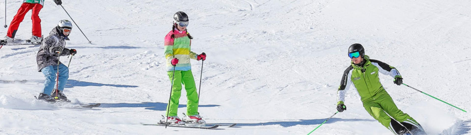 """A group of children is following its ski instructor from the ski school Ski- und Bikeschule Ötztal Sölden down the ski slope during their Kids Ski Lessons """"All-in-One"""" (11-14 years) - All Levels."""