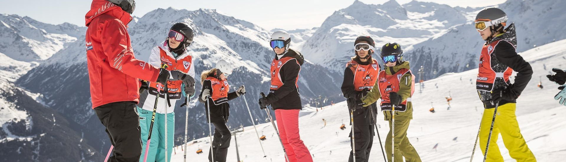 "A ski instructor and some young skiers smiling at the camera during the Kids Ski Lessons ""All-Inclusive"" (9-15 years) - All Levels organized by the ski school Ski & Snowboardschool Vacancia in the ski resort of Sölden."
