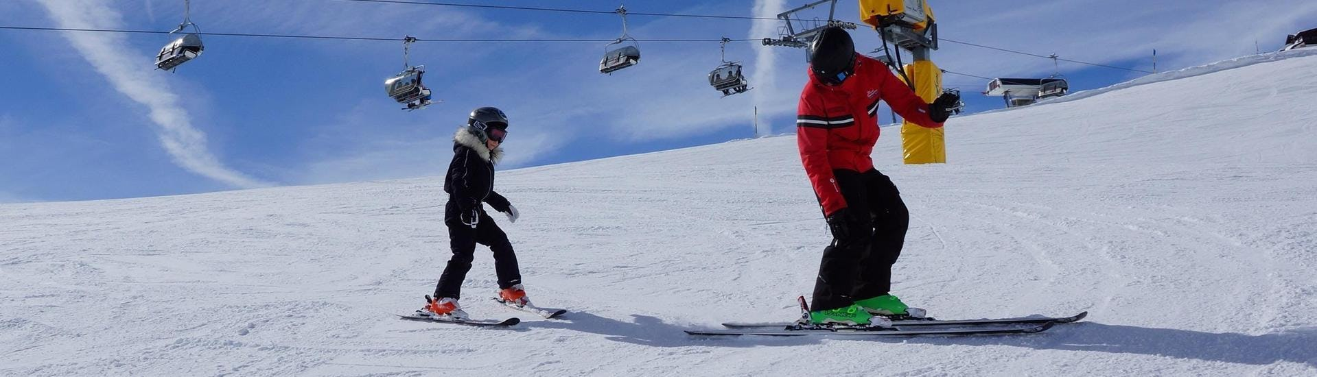"""A ski instructor from the ski school Ski- und Snowboardschule Vacancia is teaching a young child how to ski during its Kids Ski Lessons """"All-Inclusive"""" (9-15 years) - All Levels."""