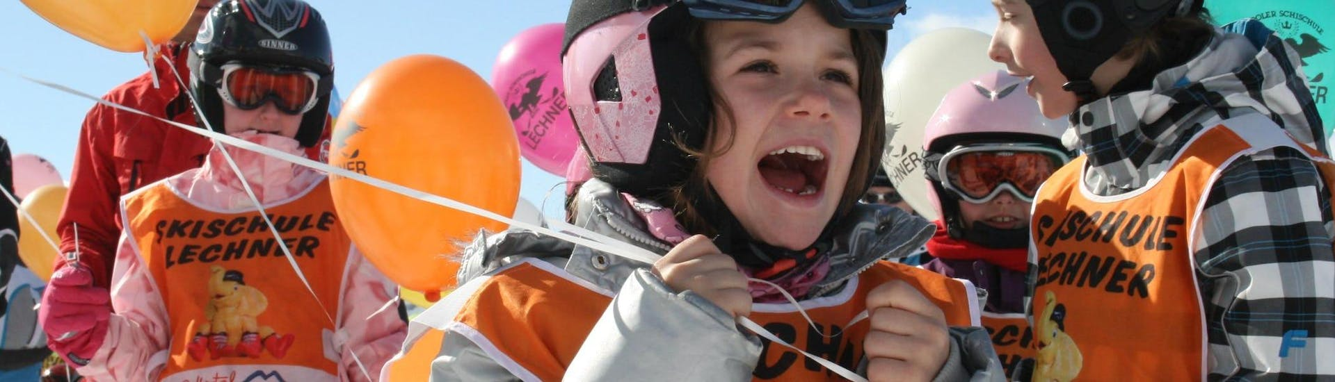 Several children taking part in the Kids Ski Lessons and Day Nursery - (3-5 years) organised by the ski school Skischule Lechner are holding balloons with the ski school's logo printed on them.