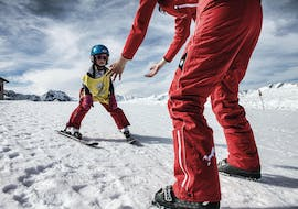"""A group of children poses together with their ski instructor from Ski School St.Gallenkirch in the snow for the picture and look forward to their Kids Ski Lessons """"Bambini"""" (3-4 y.) for First Timers."""