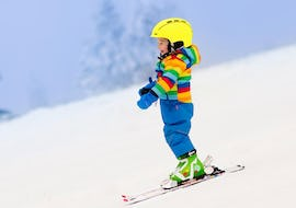"A young child in a multi-coloured jacket is skiing down one of the slopes in Zell am Ziller during their Kids Ski Lessons ""Bambini"" (3-5 years) with the ski school Skischule Pro Zell."