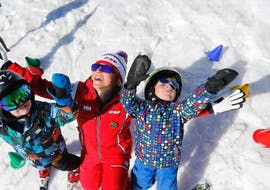 """Children are standing in the snow with their arms in the air alongside their ski instructor from the ski school ESF Alpe d'Huez during their Kids Ski Lessons """"Children's Chalet"""" (2-5 years)."""
