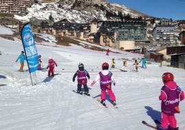 "Young skiers are learning how to ski in the safe environment of the kindergarten during their Kids Ski Lessons ""Club Mont et Souris"" (3-4 years) with the ski school ESI du Tourmalet in La Mongie."