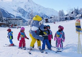 "Young skiers are learning to ski with the mascot of the ski school ESF Chamonix during their Kids Ski Lessons ""Club Piou-Piou"" (3-4 years)."