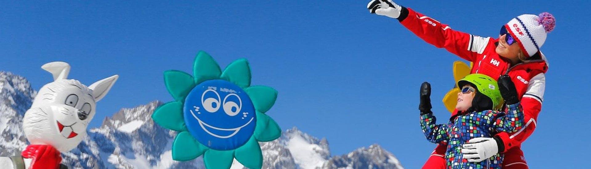 """Un petit skieur et un moniteur de ski de l'école de ski ESF Alpe d'Huez s'amusent ensemble pendant leur Cours de ski pour Enfants """"Club Piou-Piou"""" (3-5 ans)."""