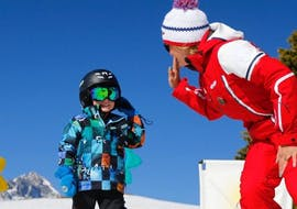 """A kid is giving a high five to his ski instructor from the ski school ESF Alpe d'Huez during his Kids Ski Lessons """"Club Piou-Piou"""" (3-5 years)."""