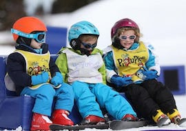 "Three little skiers are taking a break during their Kids Ski Lessons ""Club Piou-Piou"" (from 5 years) with the ski school ESF Alpe d'Huez."