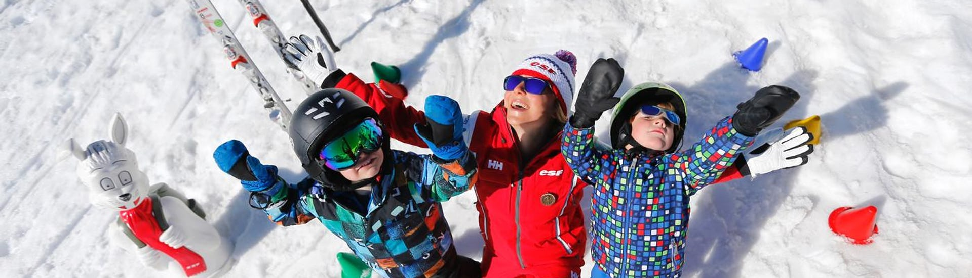 "Children are standing in the snow with their arms in the air alongside their ski instructor from the ski school ESF Alpe d'Huez during their Kids Ski Lessons ""Club Piou-Piou"" (from 5 years) - February."