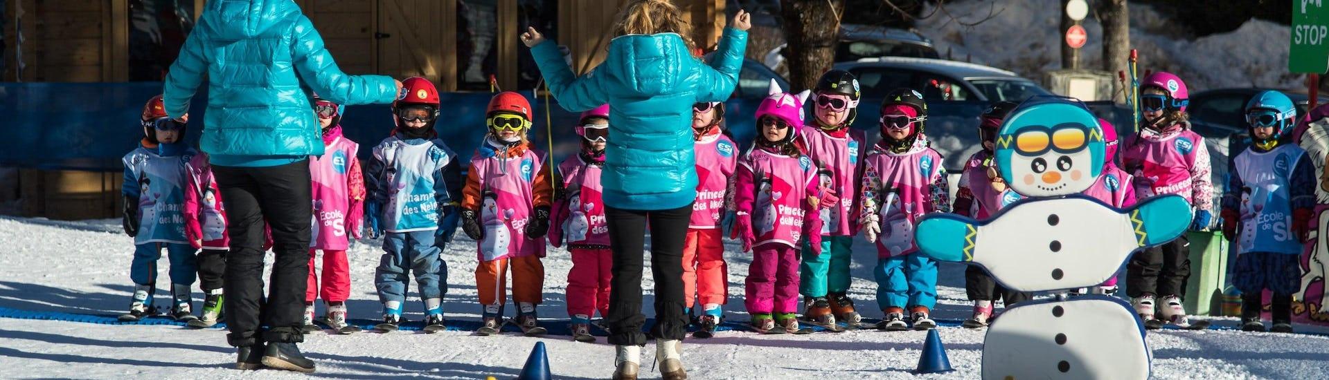 """De jeunes enfants sont les uns à côté des autres et écoutent leur moniteur de ski de l'école de ski ESI Dévoluy avant leur Cours de ski pour Enfants """"Club Souris"""" (5-7 ans)."""