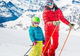 "A child is learning how to ski in the Kids Ski Lessons ""First Slopes"" (5-12 years) - Beginner in the safe environment of the ski school ESF Ski School Val d'Isère."