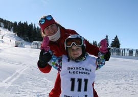 A young girl and her ski instructor from the ski school Skischule Lechner are smiling at the camera during the Kids Ski Lessons for Beginners (5-14 years).